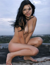 Naked dark haired babe on the roof top
